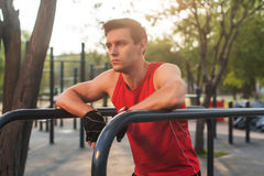Young athletic man taking a break during working out outdoor. Royalty Free Stock Images
