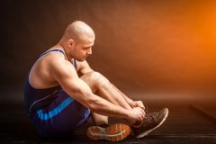 A young athletic man ties up shoelaces royalty free stock images
