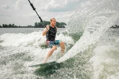 Young athletic man wakesurfing on the board holding a cable royalty free stock image