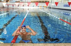 Young athletic man wearing cap and goggles. In swimming pool royalty free stock image