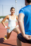 Young athletic man and woman stretching outdoors on a hot summer Stock Images