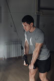 Young athletic man workout triceps on block exerciser. Royalty Free Stock Photo