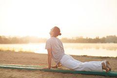 Young athletic men doing yoga on the sand in the park. Concept about people, lifestyle and sport. Yoga on the beach, near lake in the park one performer, at Stock Images