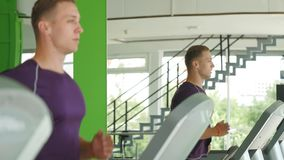 Young athletic men running on treadmill in sport gym.  stock footage