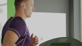 Young athletic men running on treadmill in sport gym.  stock video footage