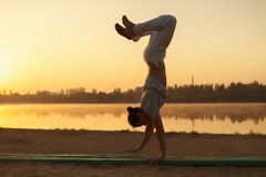 Young athletic men standing in yoga pose on near lake in the par. Concept about people, lifestyle and sport. Yoga on the beach, near lake in the park one Royalty Free Stock Photos