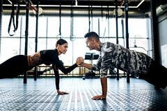 Young athletic man and woman are doing plank and holding hand in hand in the gym stock image