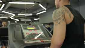 Young athletic men and women exercising and running on treadmill in sport gym. Young athletic men and women exercising and running on treadmill in sport gym stock video footage