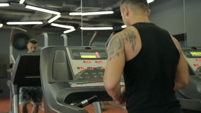Young athletic men and women exercising and running on treadmill in sport gym. Young athletic men and women exercising and running on treadmill in sport gym stock video
