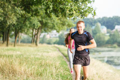 Young athletic people jogging outdoor near pond Royalty Free Stock Photo