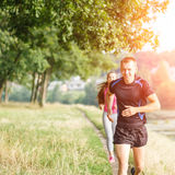 Young athletic people jogging outdoor near pond Royalty Free Stock Images