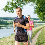 Young athletic people jogging outdoor near pond Stock Image