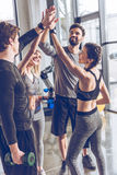 Young athletic people in sportswear giving high five in gym. Happy young athletic people in sportswear giving high five in gym royalty free stock photo
