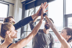 Young athletic people in sportswear giving high five in gym. Happy young athletic people in sportswear giving high five in gym Stock Photography