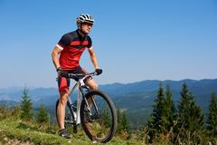 Young athletic professional sportsman starting cycling bike on top of hill stock photography