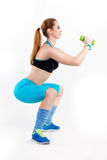 Young athletic red-haired woman in bright sportswear is doing squats Royalty Free Stock Photos