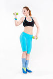 Young athletic red-haired woman in sportswear doing exercise with dumbbells. Royalty Free Stock Photos