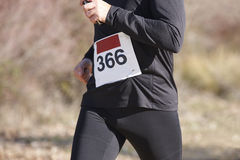 Young athletic runner on a cross country race. Outdoor circuit. Stock Photo