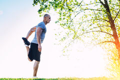 Young athletic runner doing stretching exercise, preparing for workout in the park. sunset Royalty Free Stock Photo