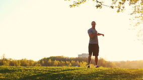 Young athletic runner doing stretching exercise, preparing for workout in the park. sunset, toned video stock video