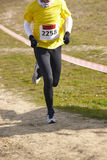 Young athletic runner with number on a race. Outdoor circuit. Stock Image