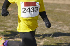 Young athletic runners on a race. Outdoor circuit. Winter time Stock Image