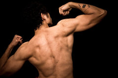 Young athletic shirtless man posing on black background Royalty Free Stock Photography