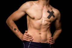 Young athletic shirtless man posing on black background Stock Photos