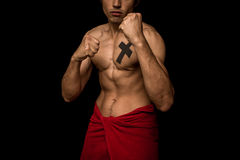 Young athletic shirtless man posing in boxing stance on black background Stock Image