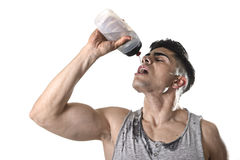 Young athletic sport man thirsty drinking water holding bottle pouring fluid on sweaty face Royalty Free Stock Photos