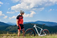 Young athletic sportsman biker in professional sportswear looking at mtb on mountain grassy hill stock images