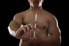 Young athletic sportsman holding syringe in sport doping and cheat concept Stock Images