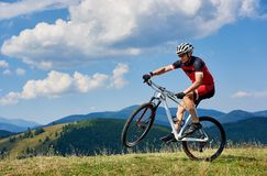 Young athletic sportsman tourist biker in professional sportswear turning on one wheel of bike. On mountain hill on bright blue sky background. Active lifestyle royalty free stock photos