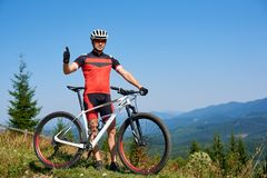 Young athletic successful tourist biker in sportswear standing at bike with thumb-up gesture royalty free stock image