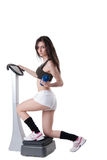 Young athletic woman advertise massage machine. Young athletic woman wear a black cotton belly top and white shorts advertise massage machine, isolated on white Royalty Free Stock Photography