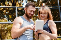Young athletic woman and bearded man browsing the internet on ta Stock Images