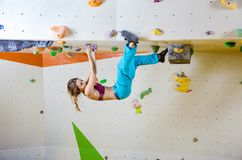 Young woman climbing upside down in bouldering gym Royalty Free Stock Images