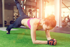 Young athletic woman doing core exercise in gym. Young athletic woman doing core exercise in the gym. Fitness woman background with sunset beams through the stock photography