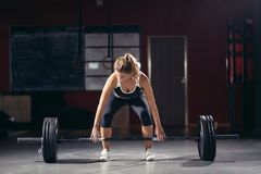 Young athletic woman doing deadlift with barbell. Intense workout in dark gym: young athletic woman doing deadlift with barbell on standing position, legs at Stock Image