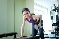 Young athletic woman doing an exercise with a dumbbell on a spor. Ts bench Stock Photos