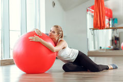 Young athletic woman doing exercises with fitness ball in gym stock image