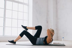 Young athletic woman doing press exercise on the mat at home. Young athletic woman doing press exercise on the grey mat at home. Focused on training girl is Stock Images