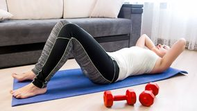 Young athletic woman doing sit-ups on fitness mat at home. Athletic woman doing sit-ups on fitness mat at home Stock Photography