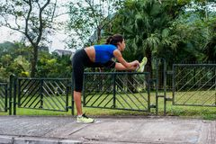 Young athletic woman doing warming-up exercises, stretching her legs on fence at road before running Royalty Free Stock Photos