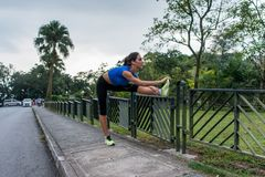 Young athletic woman doing warming-up exercises, stretching her legs on fence at road before running.  Stock Image