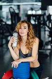 Young athletic woman drinking water in gym. Young athletic woman with red hair drinking water in gym Royalty Free Stock Photo