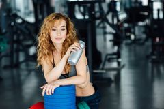 Young athletic woman drinking water in gym. Young athletic woman with red hair drinking water in gym Royalty Free Stock Photos