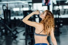 Young athletic woman drinking water in gym. Young athletic woman with red hair drinking water in gym Stock Photos