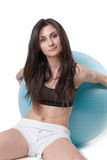 Young athletic woman exercised with a blue stability ball Royalty Free Stock Image