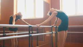 Young athletic woman gymnast doing stretching leg on barre in a studio. Close up Stock Photo